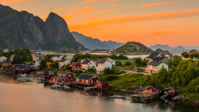 4k timelaspe sunset scene of moving clouds over traditional norwegian fisherman's cabins, rorbuer, on the island of hamnoy, reine, lofoten islands, summer of norway. - traditionally norwegian stock videos & royalty-free footage