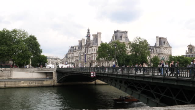 4k tourist cruise ships sailing down the river seine and under bridges as they take holiday makers on a guide of the city in paris france - river seine stock videos & royalty-free footage