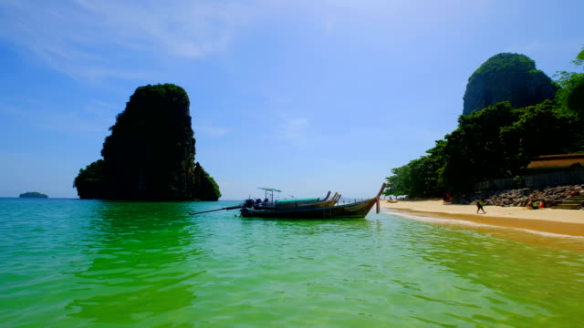 4k Tropical sand beach Andaman sea southern of Thailand and longtail boat.
