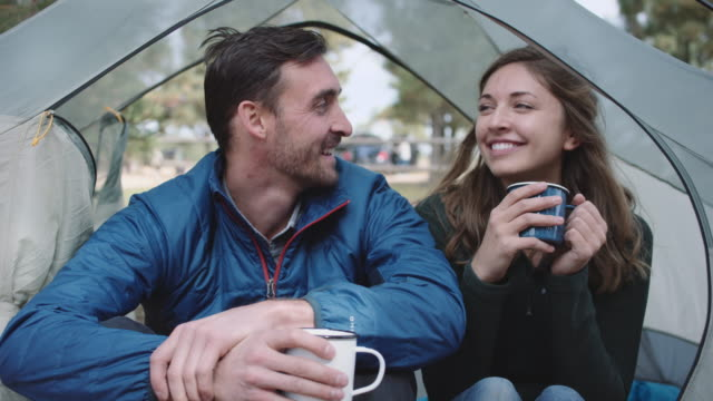 4k uhd: caucasian couple having hot drinks in their tent - camping stock videos & royalty-free footage