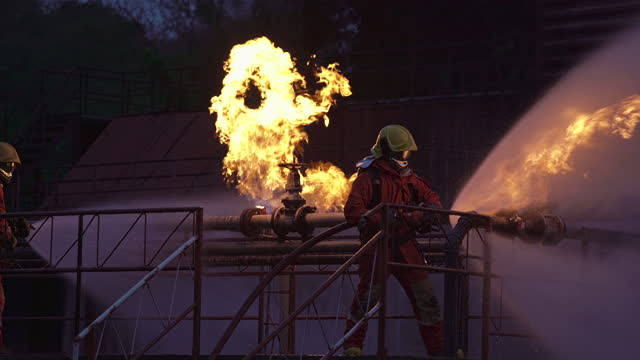 4k uhd pompiere che utilizza estintore tipo nebbia d'acqua per combattere con la fiamma antincendio da perdita di oleodotto ed esplosione su piattaforma petrolifera e stazione di gas naturale. concetto di sicurezza dei vigili del fuoco e del lavoro. - incendio video stock e b–roll