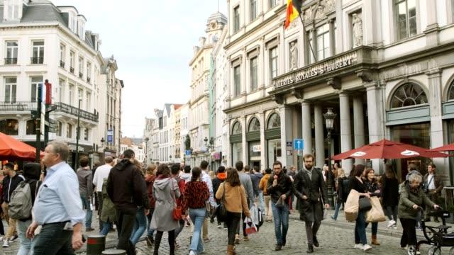 4k uhd slowmotion menge zu fuß menschen über die straße mit verkehr und fassade shop in brussel belgium berühmten ziel europas - städtischer platz stock-videos und b-roll-filmmaterial