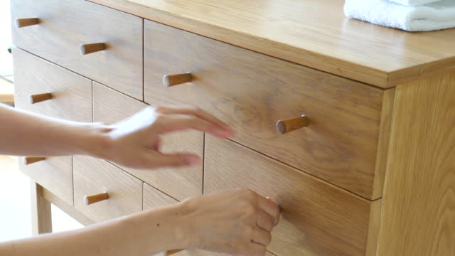 4k: Use hand pulling open drawer of cabinet.