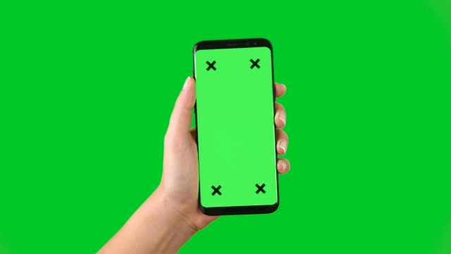 vídeos de stock e filmes b-roll de 4k using smart phone displaying chroma key on green screen - green