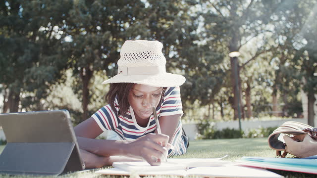4k vide footage of a young woman making notes while lying on the lawn with a digital tablet - note pad stock videos & royalty-free footage