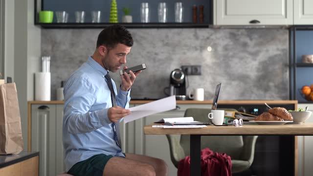 vídeos de stock, filmes e b-roll de 4k vídeo empresário trabalhando na cozinha em casa em isolamento - camisa e gravata