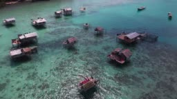 4k video footage from drone of stilt houses and boats in Sulawesi sea