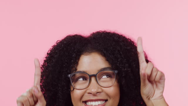 4k video footage of a beautiful young woman pointing to copyspace above her against a pink background - finger stock videos & royalty-free footage