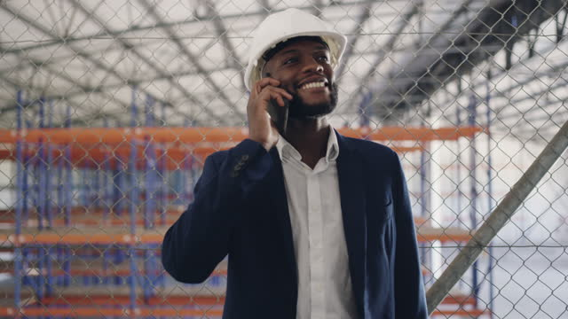 4k video footage of a businessman talking on his cellphone while working at a construction site - construction site stock videos & royalty-free footage
