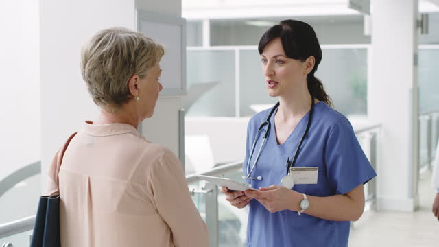 4k video footage of a doctor talking to a elderly woman in a hospital - efficiency stock videos & royalty-free footage