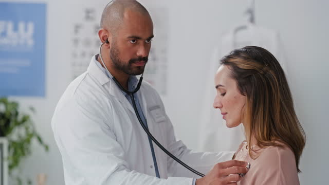 4k video footage of a doctor using a stethoscope to listen to a patient's heartbeat in an office - young men stock videos & royalty-free footage