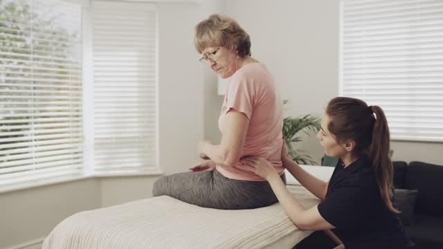 vídeos de stock, filmes e b-roll de 4k vídeo de uma fisioterapeuta do sexo feminino dando a uma paciente idosa uma massagem - dor