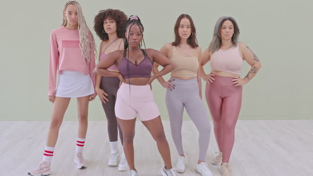 4k video footage of a group of attractive young woman posing in studio against a green background - full length stock videos & royalty-free footage