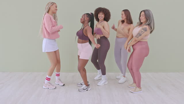 4k video footage of a group of attractive young women dancing in studio against a green background - full length stock videos & royalty-free footage