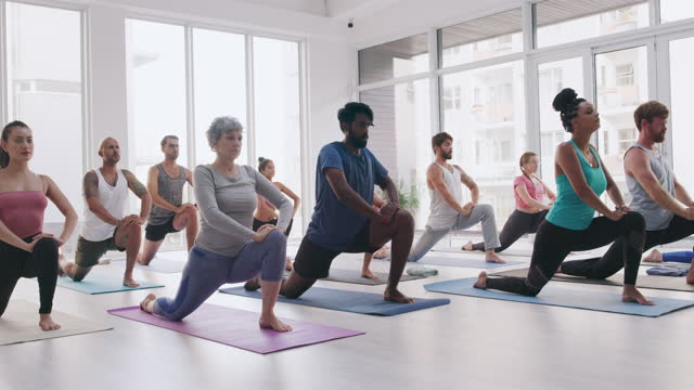 4k video footage of a group of people practising yoga in a fitness class - human limb stock videos & royalty-free footage