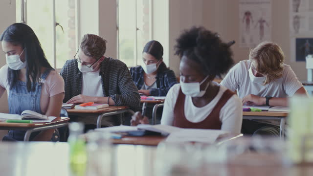 4k video footage of a group of students wearing face masks in a classroom - junior high stock videos & royalty-free footage