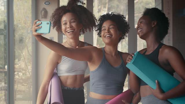 ヨガのクラス中にセルフィーを撮る若い女性のグループの4kビデオ映像 - photo messaging点の映像素材/bロール