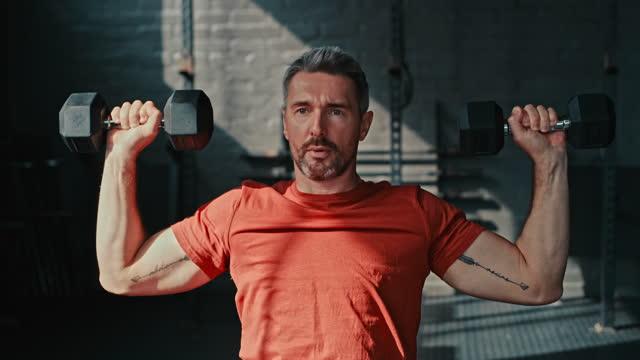 一人で座って、ジムで肩のプレスエクササイズのためにダンベルを使用してハンサムな成熟した男の4kビデオ映像 - 中年の男性一人点の映像素材/bロール