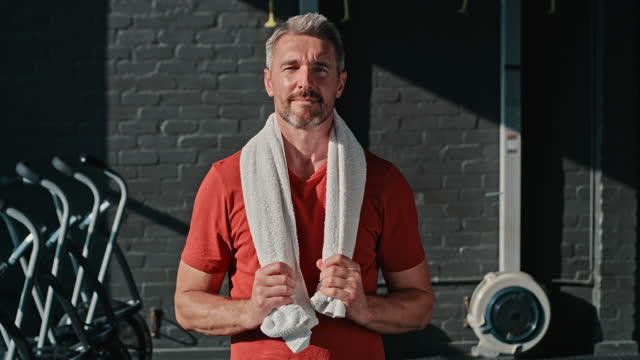 4k video footage of a handsome mature man standing alone after his workout in the gym - towel stock videos & royalty-free footage
