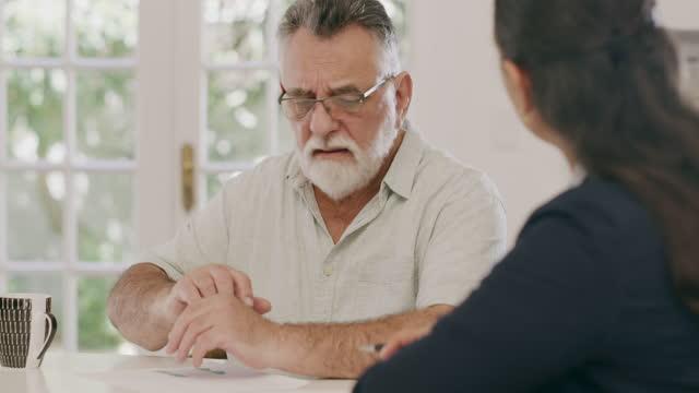 4k videofilmer av en stilig senior man som sitter med sin kvinnliga ekonomiska rådgivare hemma - råd bildbanksvideor och videomaterial från bakom kulisserna