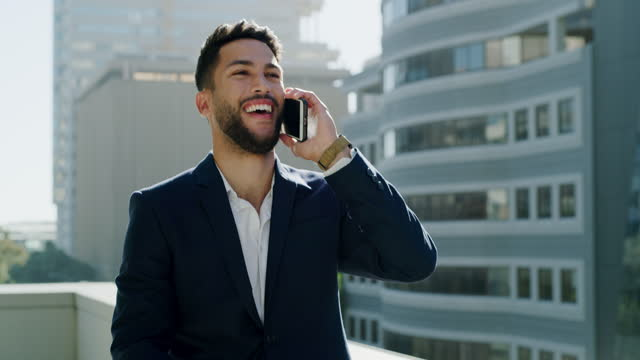 4k video footage of a handsome young businessman making a phonecall while outside on his office balcony - brown hair stock videos & royalty-free footage