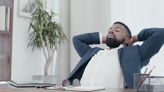 4k video footage of a handsome young businessman putting his hands behind his head after a good day's work in the office - hands behind head stock videos & royalty-free footage