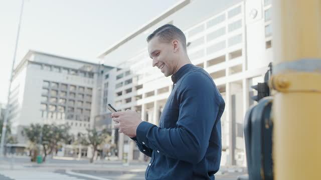 vídeos de stock, filmes e b-roll de 4k vídeo de um belo jovem empresário enviando um texto durante seu trajeto matinal pela cidade - cruzar