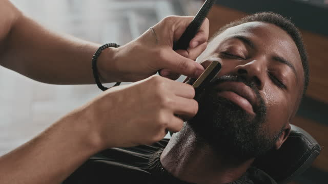 4k video footage of a handsome young man sitting in a barbershop and getting his beard shaved by a barber - beard stock videos & royalty-free footage