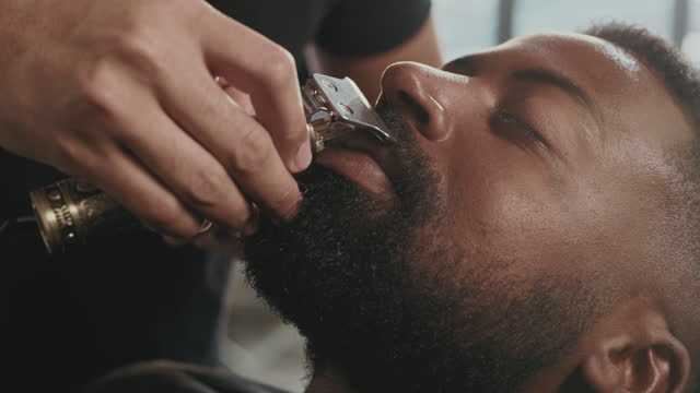 4k video footage of a handsome young man sitting in a barbershop and getting his moustache shaved by a barber - beard stock videos & royalty-free footage