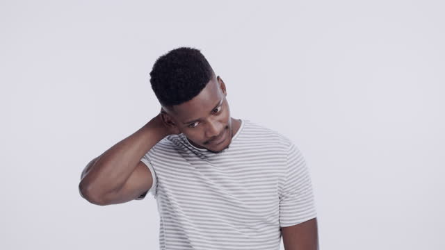 stockvideo's en b-roll-footage met 4k video footage of a handsome young man standing alone against a white background in the studio and feeling embarrassed - gezichtsuitdrukking