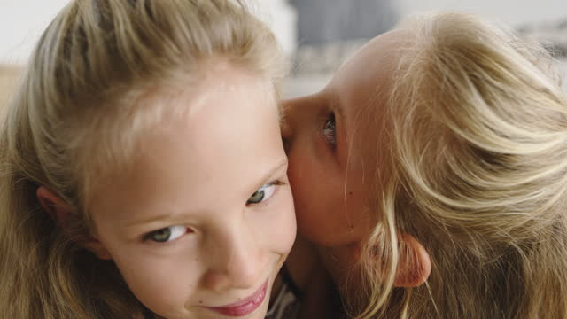 4k video footage of a little girl whispering into her sister's ears - whispering stock videos & royalty-free footage