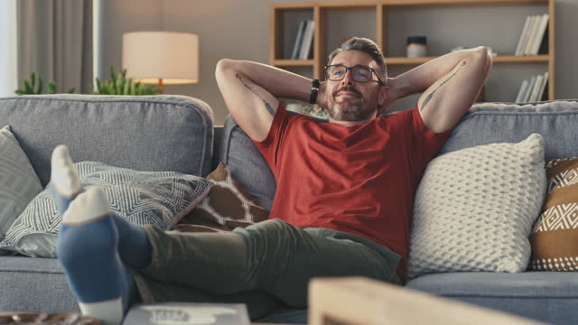 4k video footage of a man relaxing on his couch watching tv at home - remote control stock videos & royalty-free footage