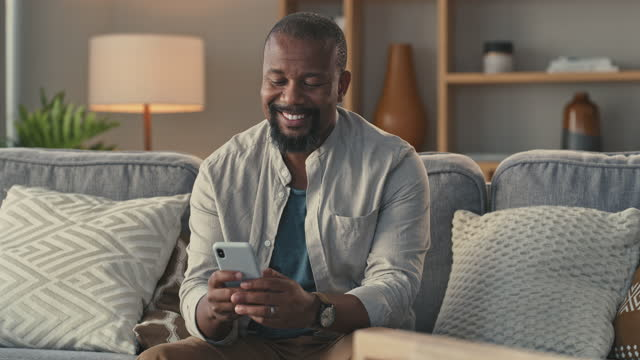 4k video footage of a man relaxing on his couch while using his cellphone to text - text stock videos & royalty-free footage