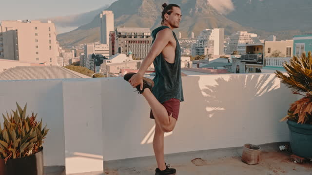 4k video footage of a man stretching during his workout on a rooftop - tank top stock videos & royalty-free footage