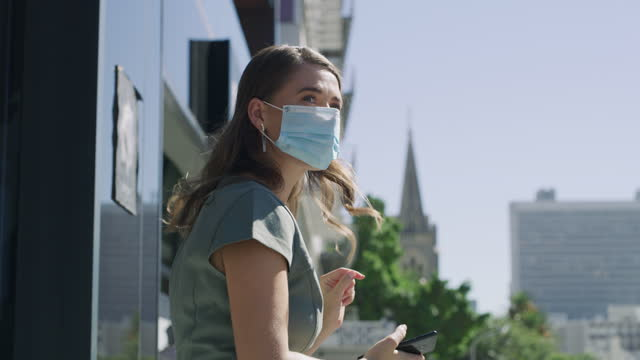 4k video footage of a masked young businesswoman using a smartphone and waving against an urban background - geographical locations stock videos & royalty-free footage
