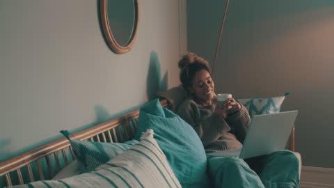 4k videofilmer av en maskerad ung kvinna som använder en bärbar dator och fikar på soffan hemma - afroamerikanskt ursprung bildbanksvideor och videomaterial från bakom kulisserna