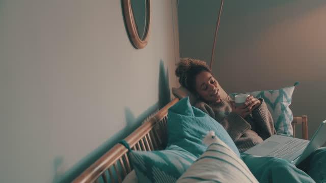 stockvideo's en b-roll-footage met 4k videobeelden van een gemaskerde jonge vrouw die laptop met behulp van en koffie op de bank thuis - resting