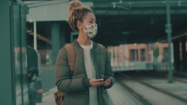 4k video footage of a masked young woman using a smartphone while walking through the city - rucksack stock videos & royalty-free footage