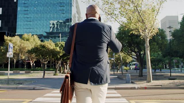 vídeos de stock, filmes e b-roll de vídeo 4k de um empresário maduro falando em um celular enquanto caminhava por uma rua na cidade - cruzar