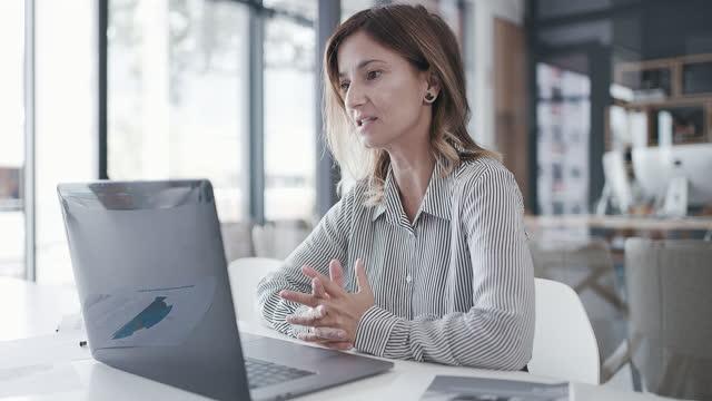vídeos de stock, filmes e b-roll de vídeo 4k de uma empresária madura tendo uma chamada de vídeo em um laptop em um escritório - bem vestido