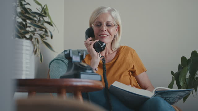 4k video footage of a mature woman sitting alone at home and using a telephone - landline phone stock videos & royalty-free footage