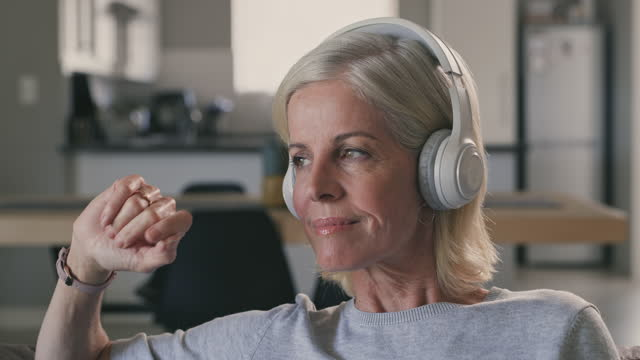 4k videoaufnahmen einer reifen frau, die zu hause auf ihrem sofa sitzt und musik über ihre kopfhörer hört - erwachsener über 40 stock-videos und b-roll-filmmaterial