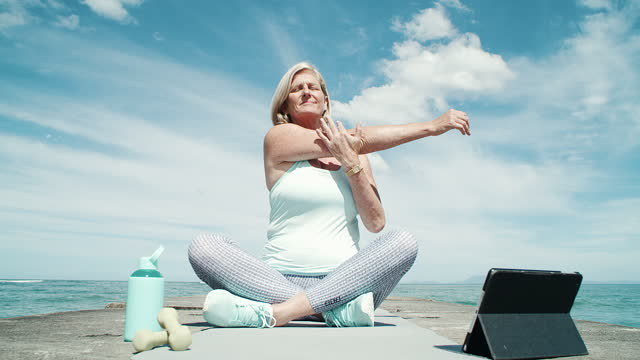 4k video footage of a mature woman using a digital tablet while practising yoga at the beach - human limb stock videos & royalty-free footage