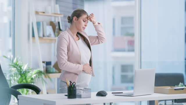 4k video footage of a pregnant young woman feeling unwell while using a laptop in a modern office - nausea stock videos & royalty-free footage