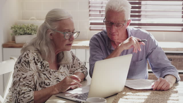 4k video footage of a senior couple sitting in their kitchen at home and using technology to calculate their finances - take that stock videos & royalty-free footage