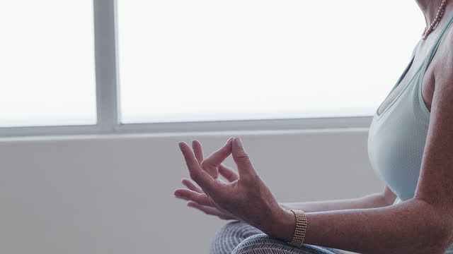 4k video footage of a senior woman doing yoga at home - yoga stock videos & royalty-free footage