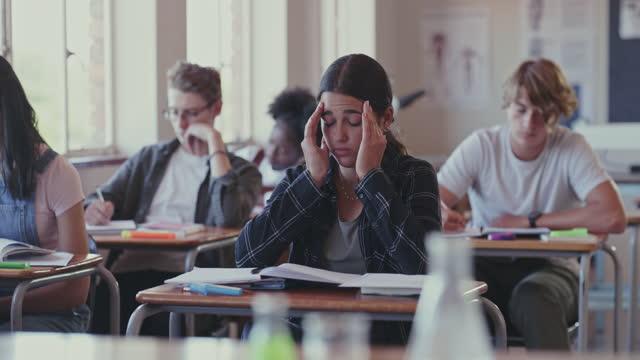 stockvideo's en b-roll-footage met 4k videobeelden van een student die worstelt met schoolwerk in een klaslokaal - exam