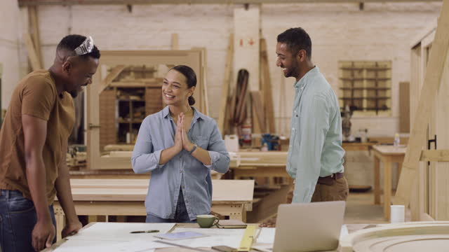 4k video footage of a team of designers giving each other a high five while working in a workshop - other stock videos & royalty-free footage