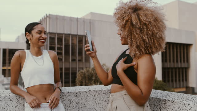 4k video footage of a two young woman taking photos in the city - female friendship stock videos & royalty-free footage