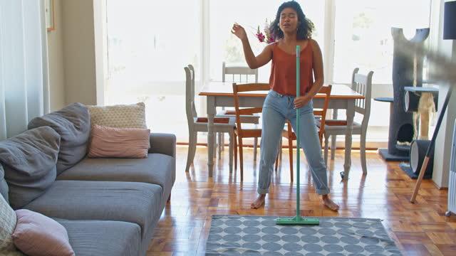 vídeos y material grabado en eventos de stock de imágenes de video 4k de una mujer escuchando música y disfrutando mientras hace tareas en casa - barrer